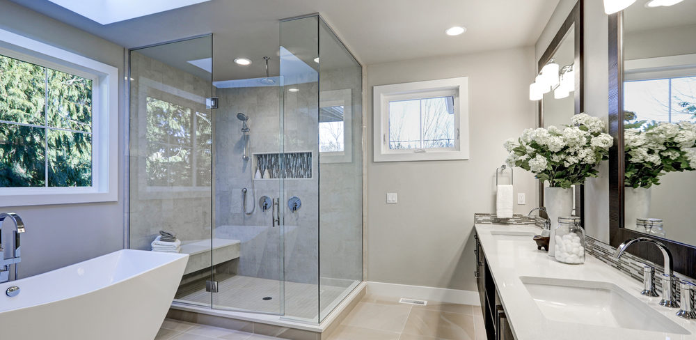 Spacious bathroom in gray tones with heated floors, freestanding tub, walk-in shower, double sink vanity and skylights.